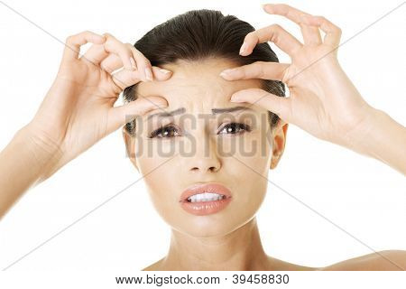 Woman checking her wrinkles on her forehead - isolated on white