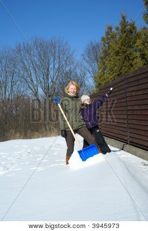 Mother And Her Daughter Throw Up Snow On A Winter Background