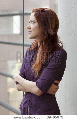 businesswoman standing at window smling - gazing upward