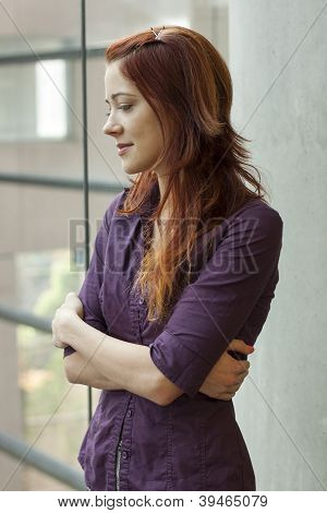 businesswoman standing at window smling - looking down