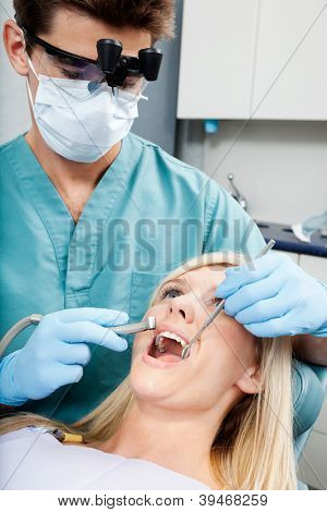Male dentist treating a young female patient at clinic