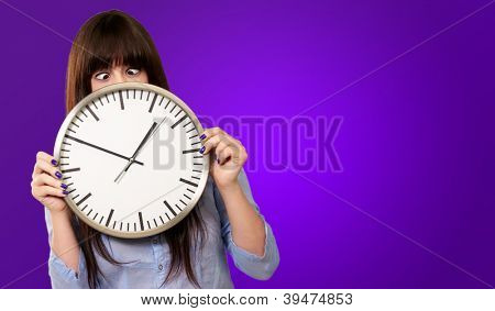 Woman Holding Clock With Squinted Eyes Isolated On Purple Background