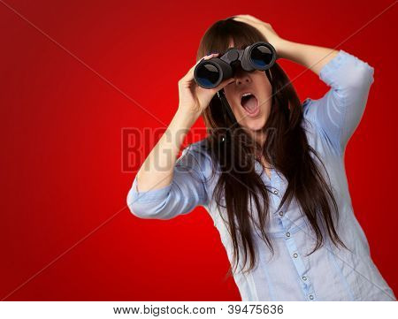 Portrait Of A Young Woman Looking Through Binoculars On Red Background