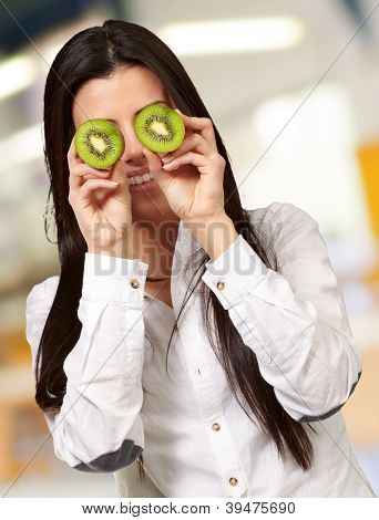 Young girl holding slices of kiwi, indoor
