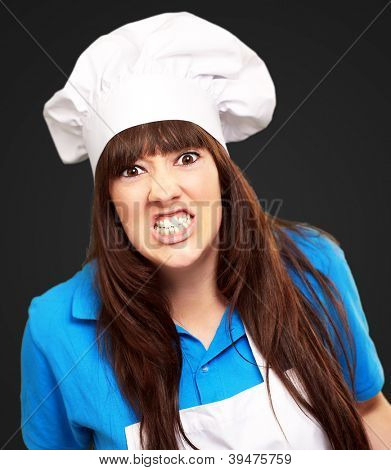 portrait of a female chef clenching on black background