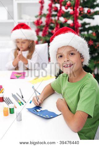 Kinder Weihnachten und saisonale Grußkarten vor den geschmückten Baum