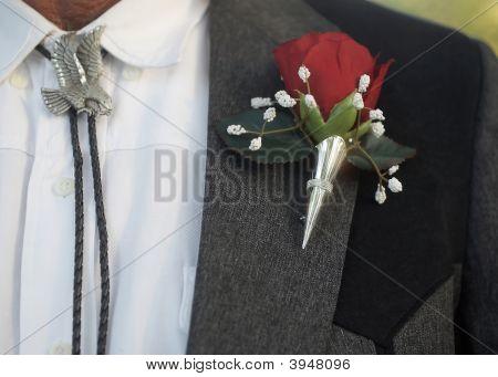 Flor en el ojal con corbata de Bolo