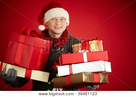 Portrait of happy man in Santa cap holding giftboxes and smiling at camera