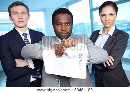 Portrait of African businessman tearing contract while looking at camera with two partners near by