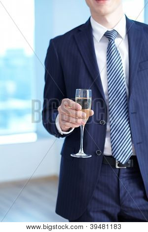 Close-up of businessman in suit holding flute of champagne in hand