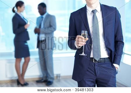 Close-up of businessman in suit holding flute of champagne