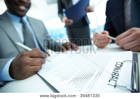 Image of contract on workplace and group of partners making decision to sign it