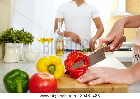 Close-up of young female cutting red pepper in the kitchen