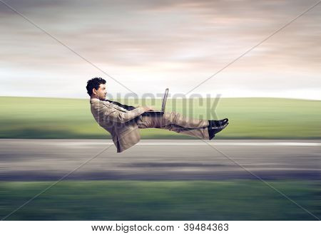 Fast levitating businessman, on a road, using a laptop computer