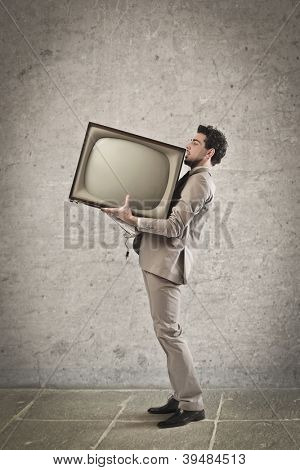 Young man holding a CRT television
