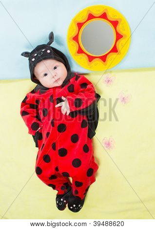 Pretty Baby Girl, Dressed In Ladybug Costume On Green Background  The Concept Of Childhood And Holid