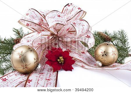 Christmas bow, ornaments, poinsettia flower, pine greens on white