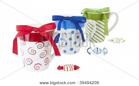 Colorful ceramic mugs with bows and candy on white