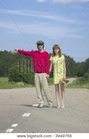 The Young Couple Stops The Car On Road