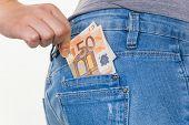 Постер, плакат: рука молодой женщины потянув евро записку из кармана ее джинсы