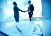 stock photo of congrats  - Image of business contract on background of two employees handshaking - JPG