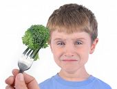 picture of rejection  - A young boy is making a funny disgusting face at a fork with a healthy piece of broccoli on a white background - JPG