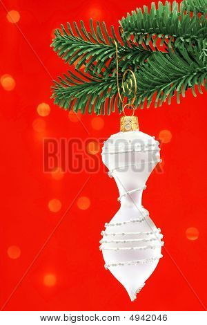 White Finial Shaped Cristmas Ornament Over Red Background On Noble Pine Tree Bough