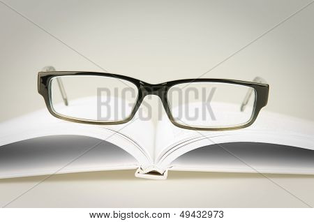 glasses on white book