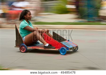 Motion Blur Of Girl Steering Car In Soap Box Derby