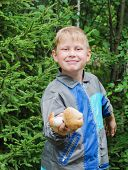 stock photo of face-fungus  - The joyful boy shows mushrooms which has found - JPG