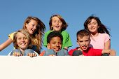 stock photo of pre-adolescent child  - group of happy smiling kids holding blank sign or banner - JPG