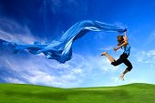 stock photo of beautiful women  - Beautiful athletic woman jumping on a green meadow with a scarf - JPG