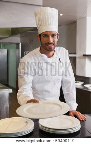 Happy head chef offering a plate smiling at camera in a commercial kitchen