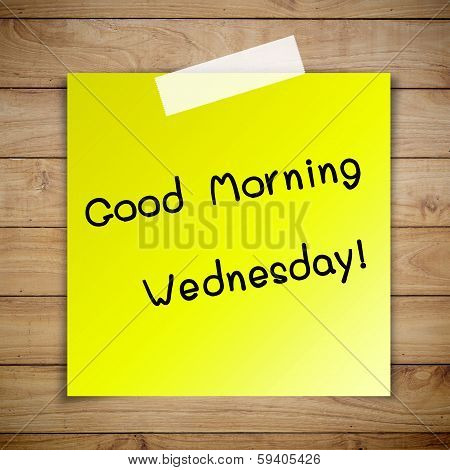 Good morning wednesday on sticky paper on Brown wood plank wall texture background