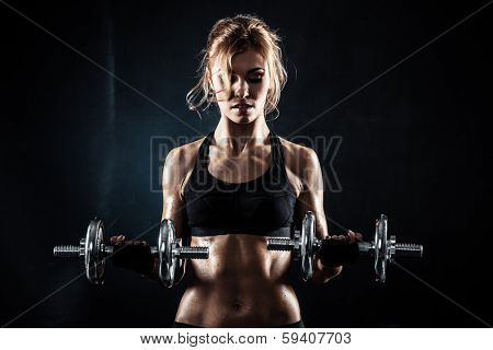 Brutal athletic woman pumping up muscules with dumbbells