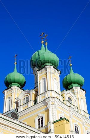 Green domes of Orthodox church against the blue sky