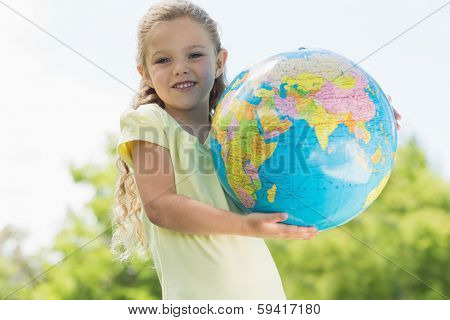 Portrait of a cute young girl holding globe at the park