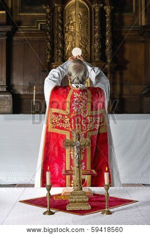 Priest during consecration the old way, with his back to the people, in a medieval church with 17th century interior