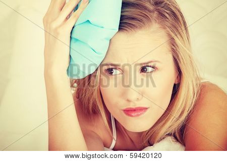 Sick woman in bed with headache