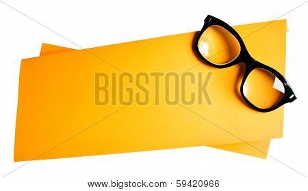 Vintage black framed eyeglasses on orange creative support.