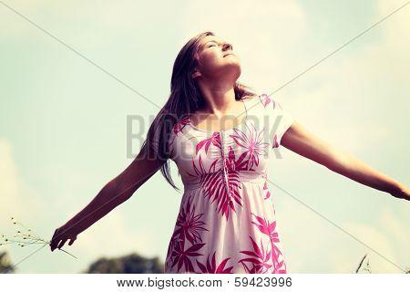 Smile teen open hands standing on field ful of flowers