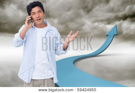 Clueless male on his cellphone against blue arrow pointing up against sky