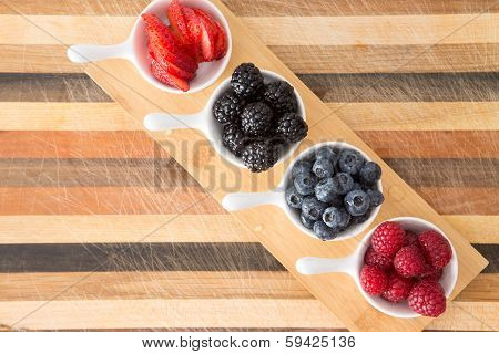 Dishes Of Fresh Berries On Decorative Striped Wood