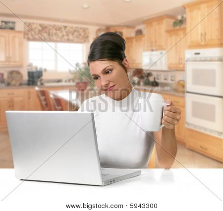 Young Woman Holding Coffee While Working On Her Laptop Computer