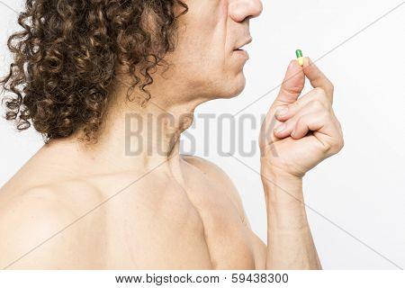 Cropped shot of bare chested mediterranean man taking colourful pill