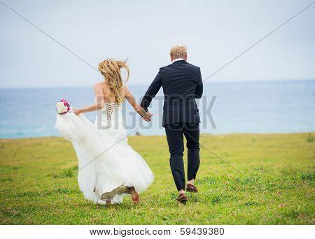 Wedding Couple, Happy romantic bride and groom in love running through field