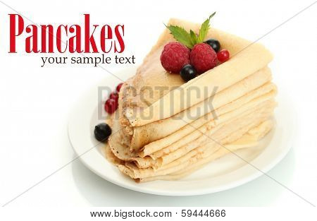 Delicious pancakes with berries and honey on plate on wooden table