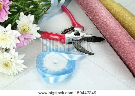 Garden secateurs and flowers isolated on white
