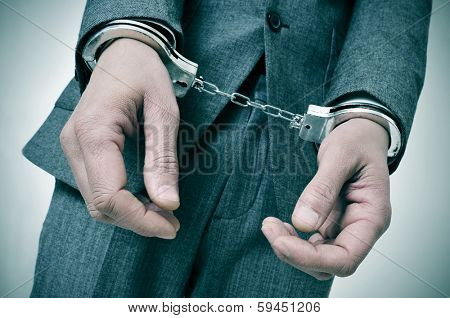 a man wearing a suit with handcuffs in his wrists