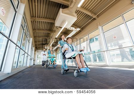 Low angle view of nurses pushing patients on wheelchairs while walking with doctor at corridor in hospital